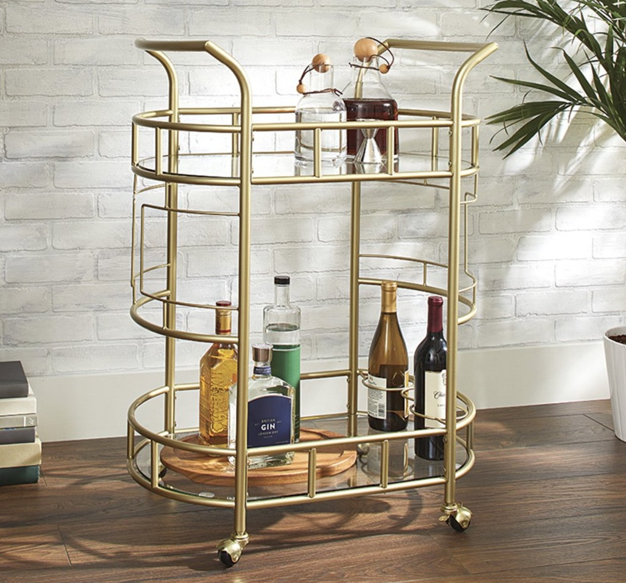 round gold bar cart with glass shelves and caster wheels