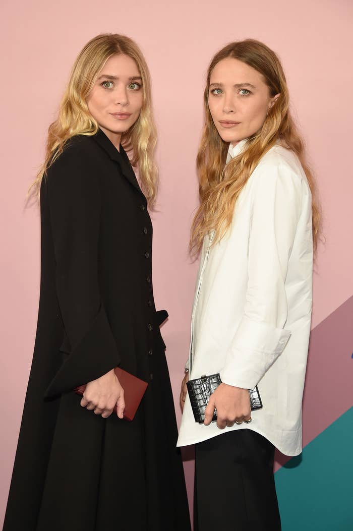 Ashley, in a long black coat, and Mary-Kate, in a white blazer and black pants, stand next to each other at the CFDA Fashion Awards in 2017