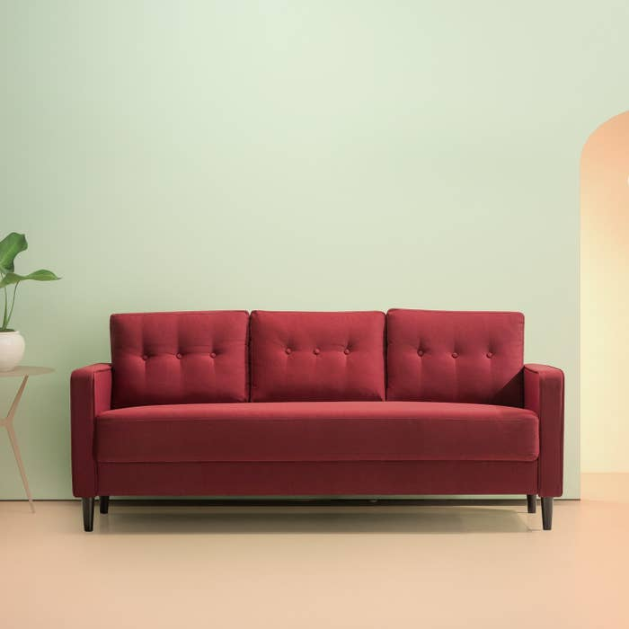 The long red couch with three tufted back cushions and square arms