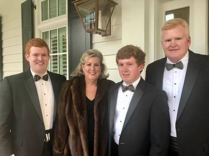 Three white men in tuxedos stand with a white woman in a fur coat