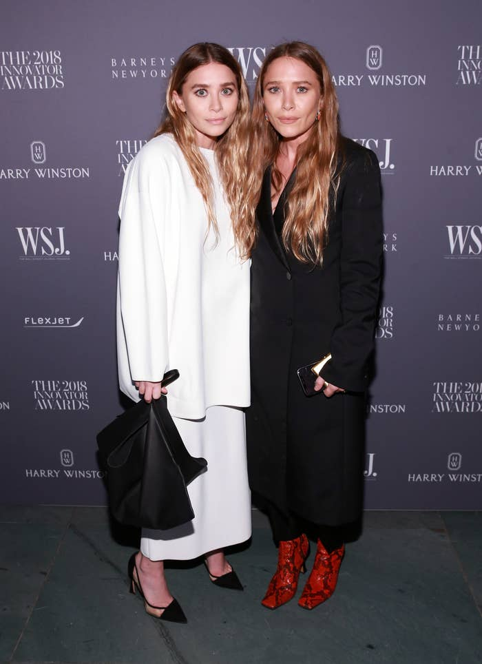 Ashley in a white dress and Mary-Kate in a black dress stand next to each other at the WSJ Magazine Innovator Awards in 2018