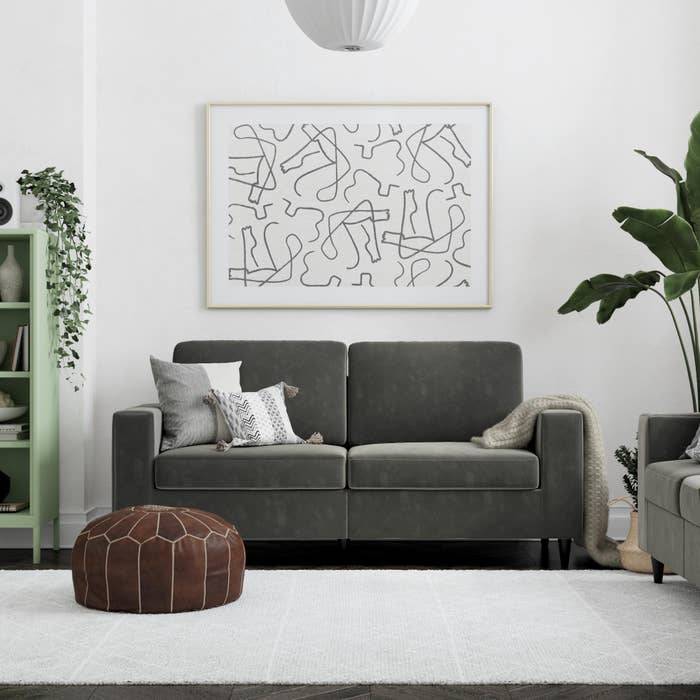 The gray velvet couch with two cushions and square arms in a living room