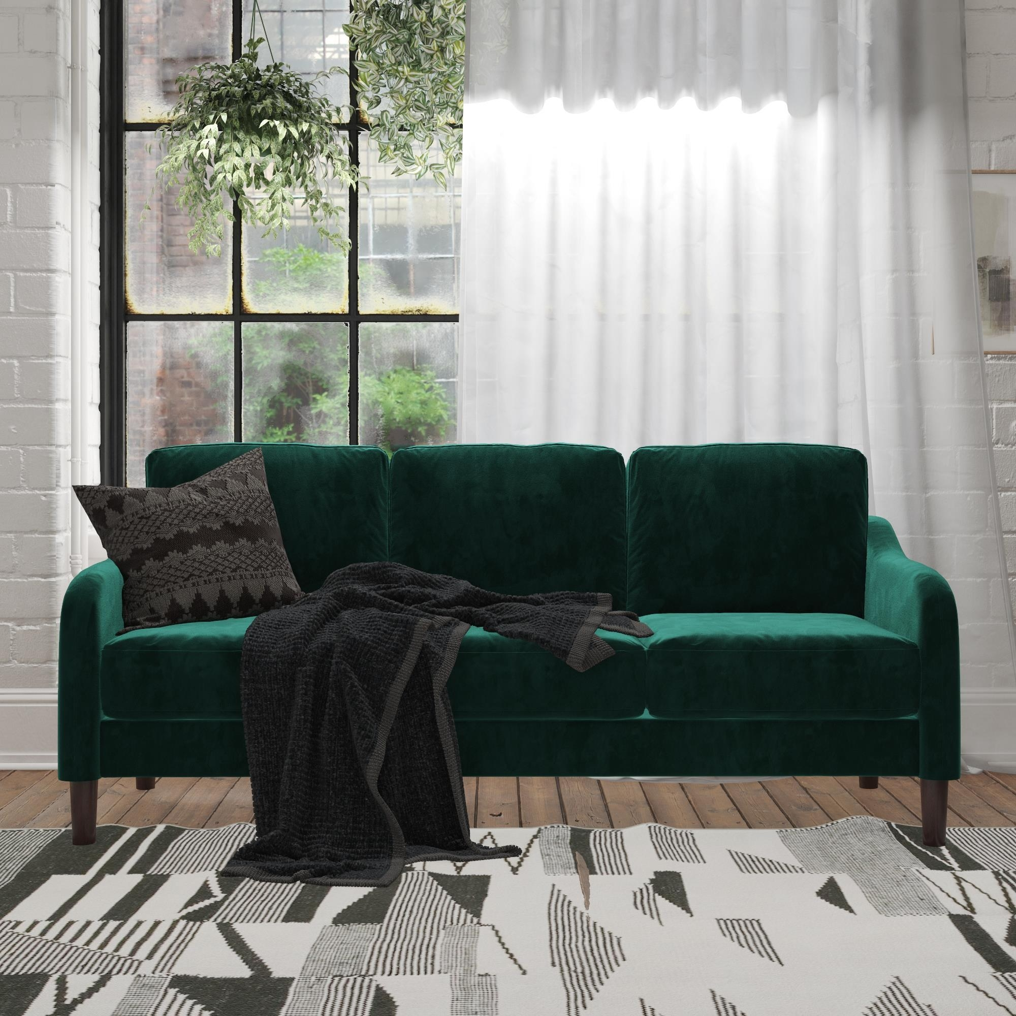 The green velvet couch with three cushions and brown legs in a living room