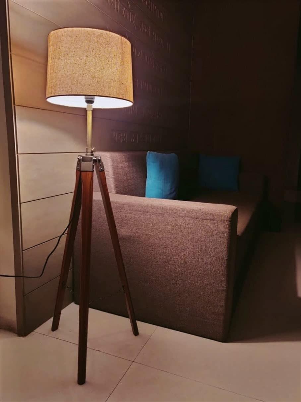 A tripod floor lamp next to a sofa