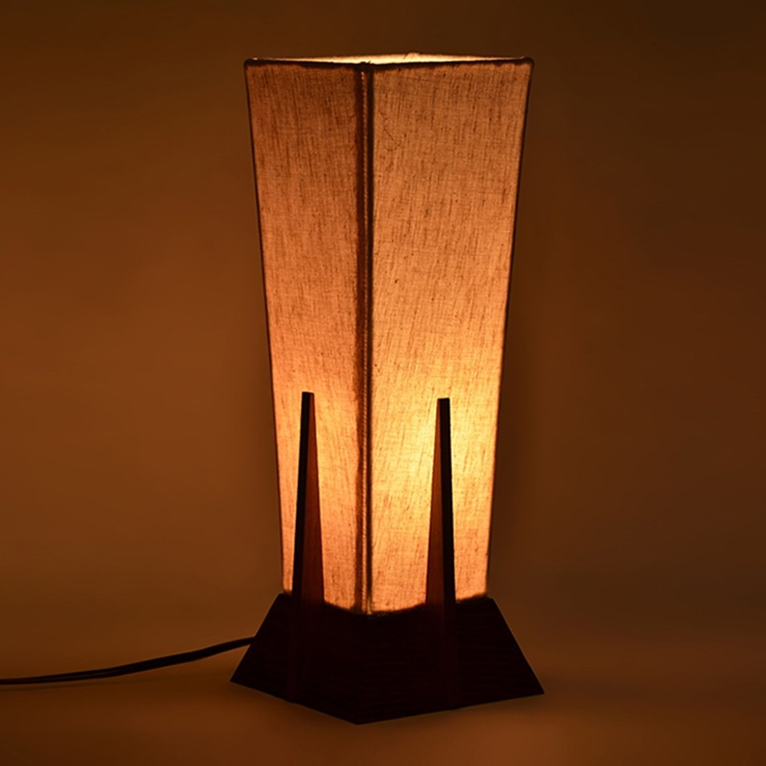 A sheesham lamp in the shape on an inverted pyramid kept on a table