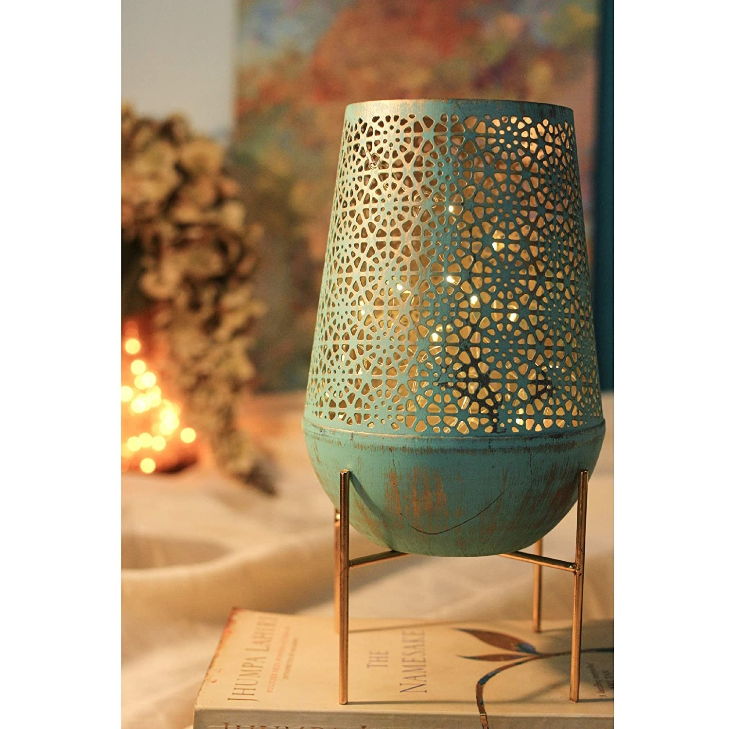 A sea green Moroccan lamp on top of a book