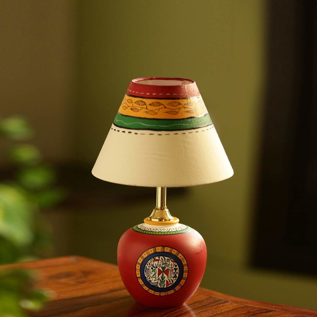 A red terracotta lamp with Warli paintings on it