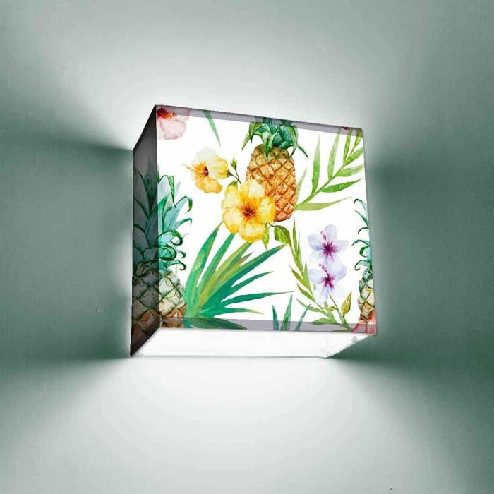 A lamp with a pineapple and some flowers and plants on it
