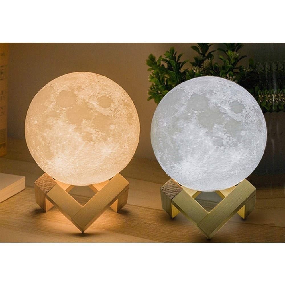 Two moon lamps, one orange and one white on a stand