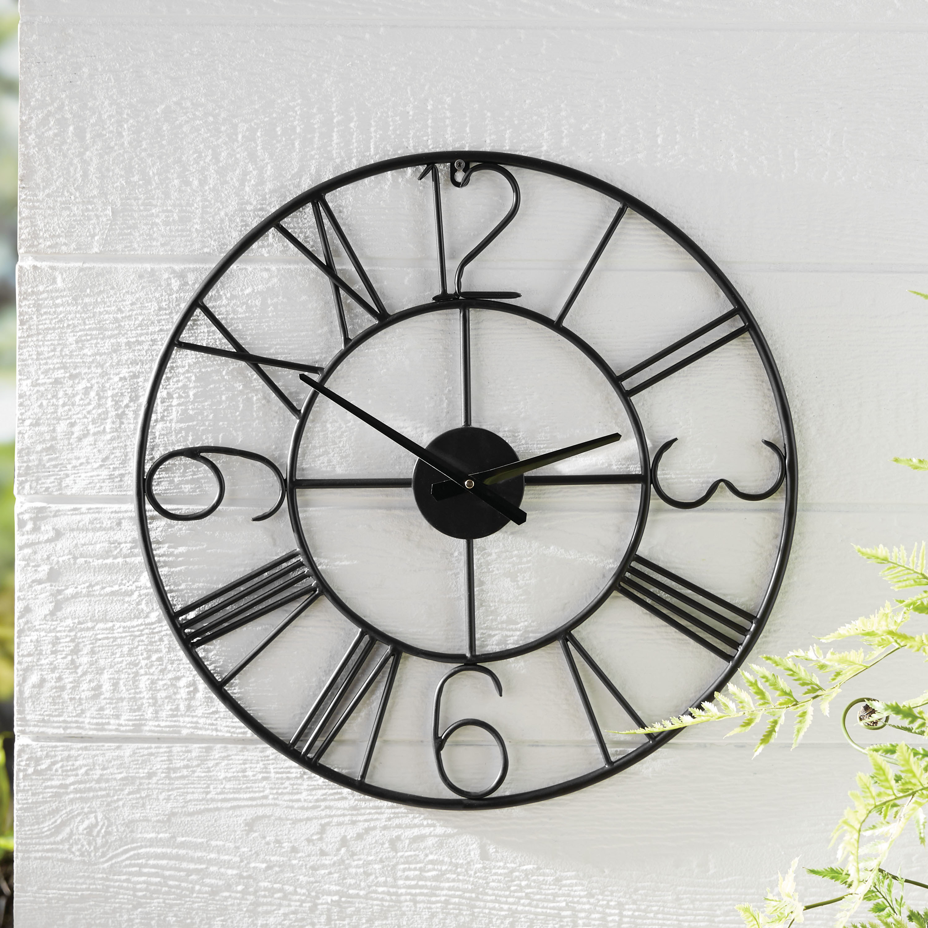 black metal clock with roman numerals and numbers for 3, 6, 9, and 12