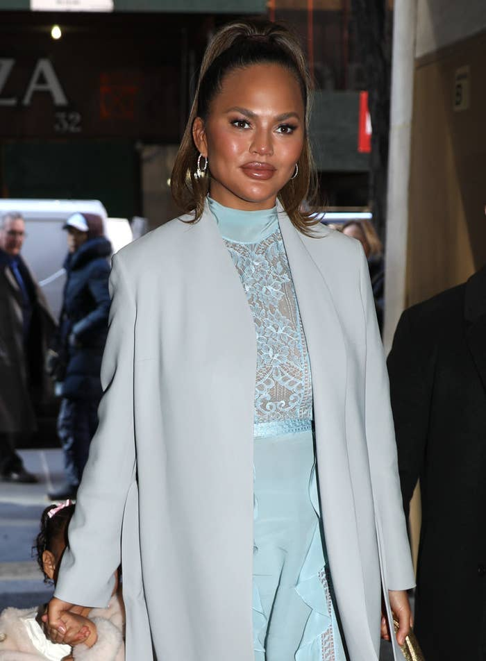 Chrissy Teigen wears a gray coat and blue dress while holding her daughter's hand in New York City in 2020