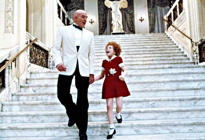 Annie and Daddy Warbucks descend a staircase while singing