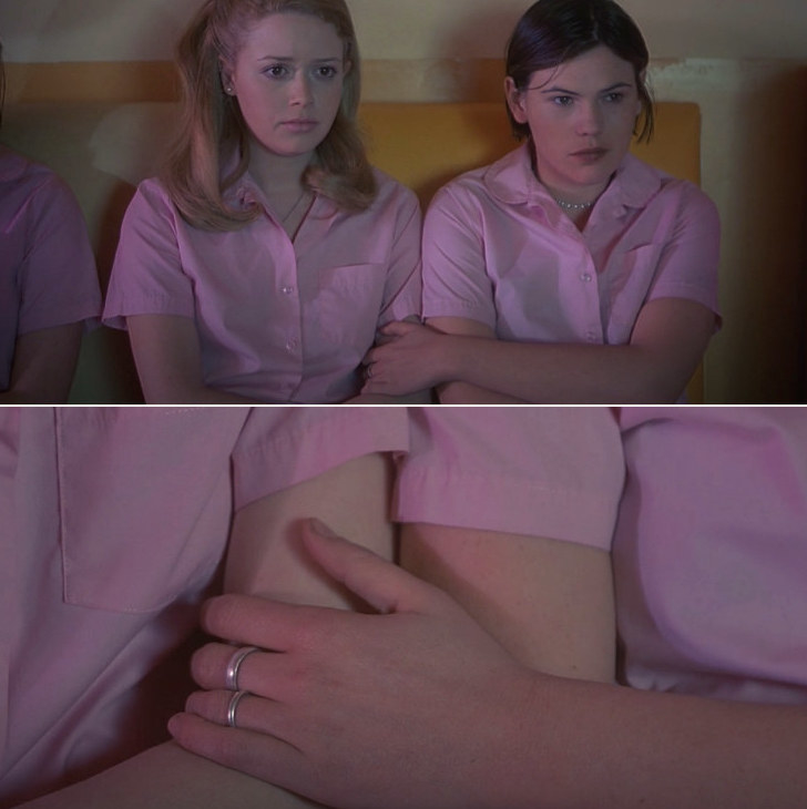 Two women sit next to each other, and one lovingly places her hand on the other woman's arm