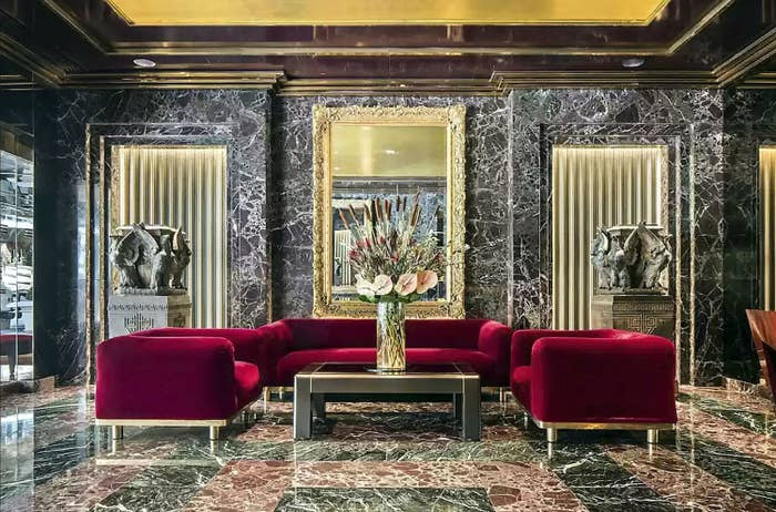 Marble walls and statues flanking a couch