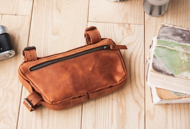 a leather saddle bag with three looped buckles you can attach to a bike