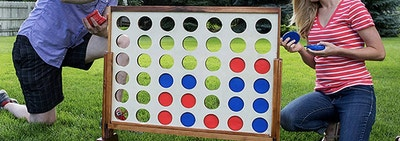 people playing a giant 4 Connect game in a backyard