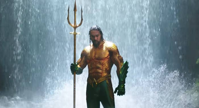 Aquaman stands in the middle of a waterfall while wearing his iconic gold and green costume while holding a giant triton.