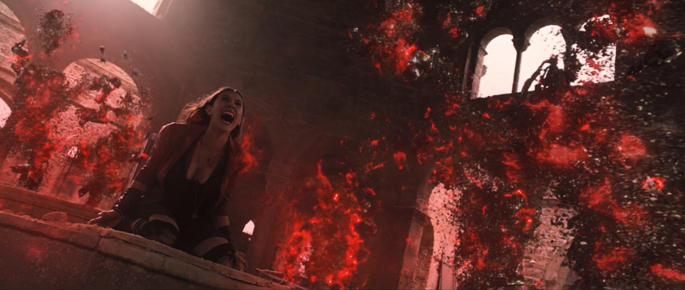 Wanda Maximoff falls to her knees as an explosion of red energy destroys the robot army around her.