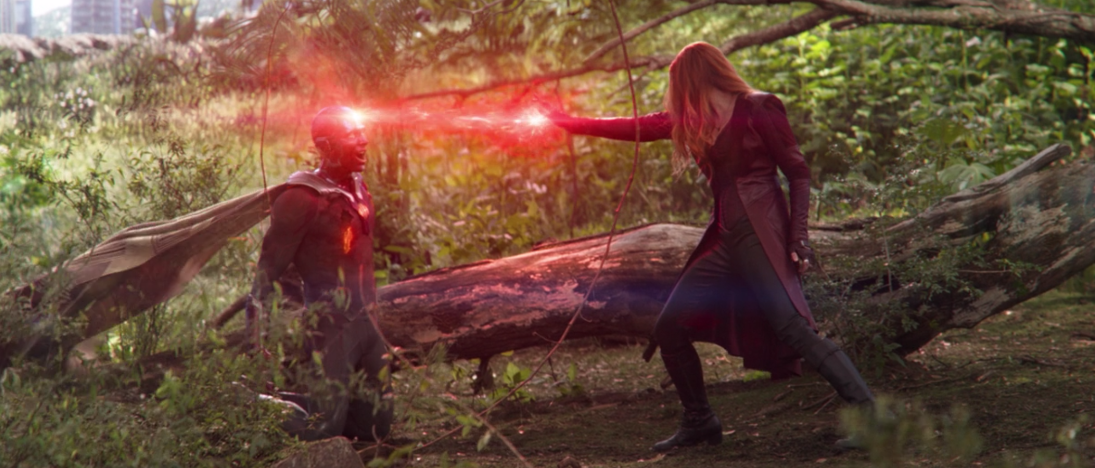 Wanda Maximoff stands with her arm outstretched and magic flowing out of her hand into the Infinity Stone located in Vision's forehead.
