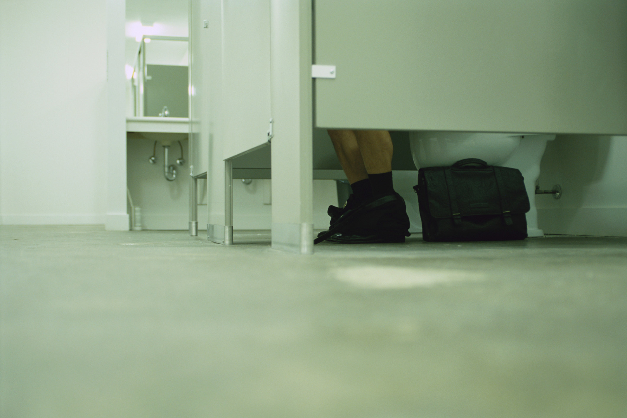 Floor level view of a public restroom, visible legs in the closest stall with pants around ankles