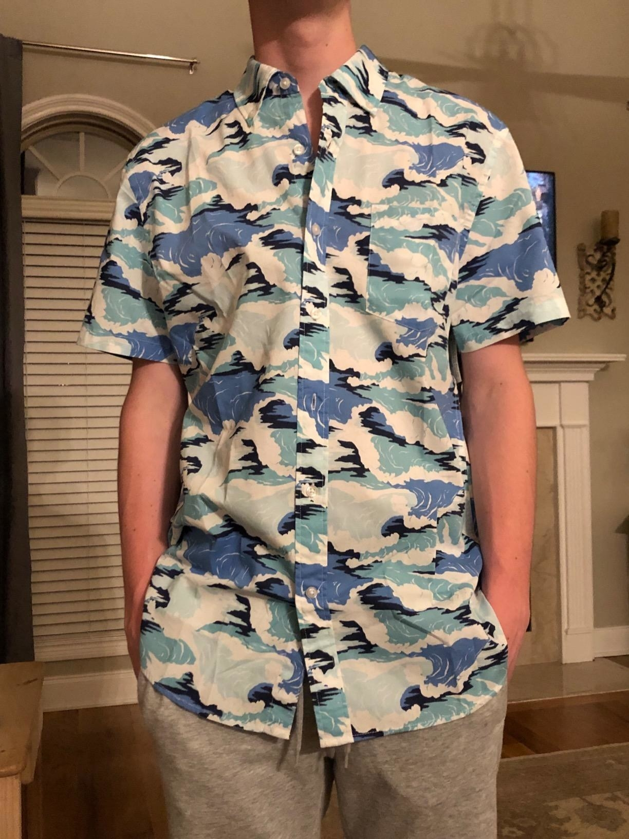 A reviewer wears the shirt with a wave pattern on it