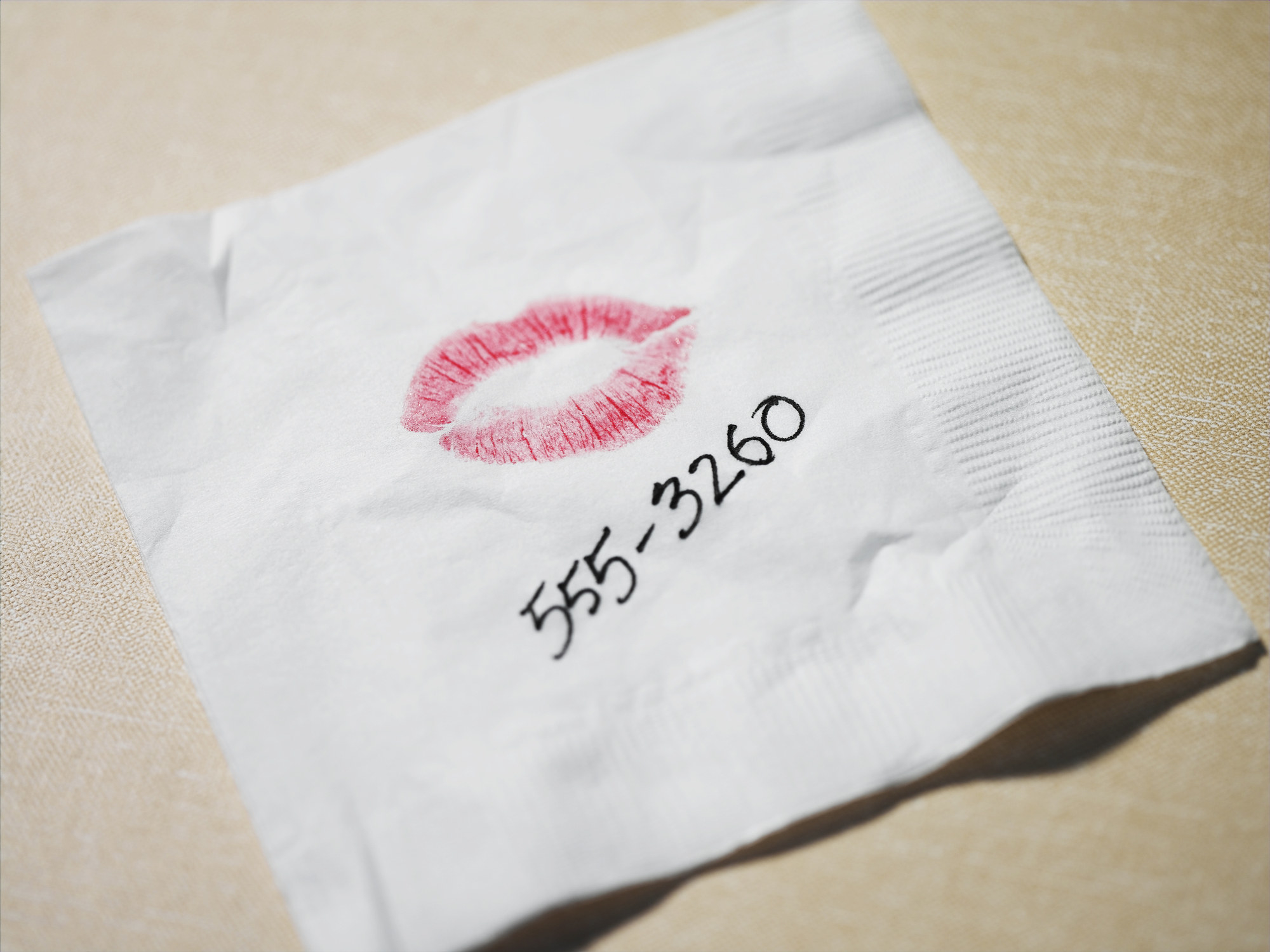 Cocktail napkin with lipstick kiss and number written in pen 555-3260
