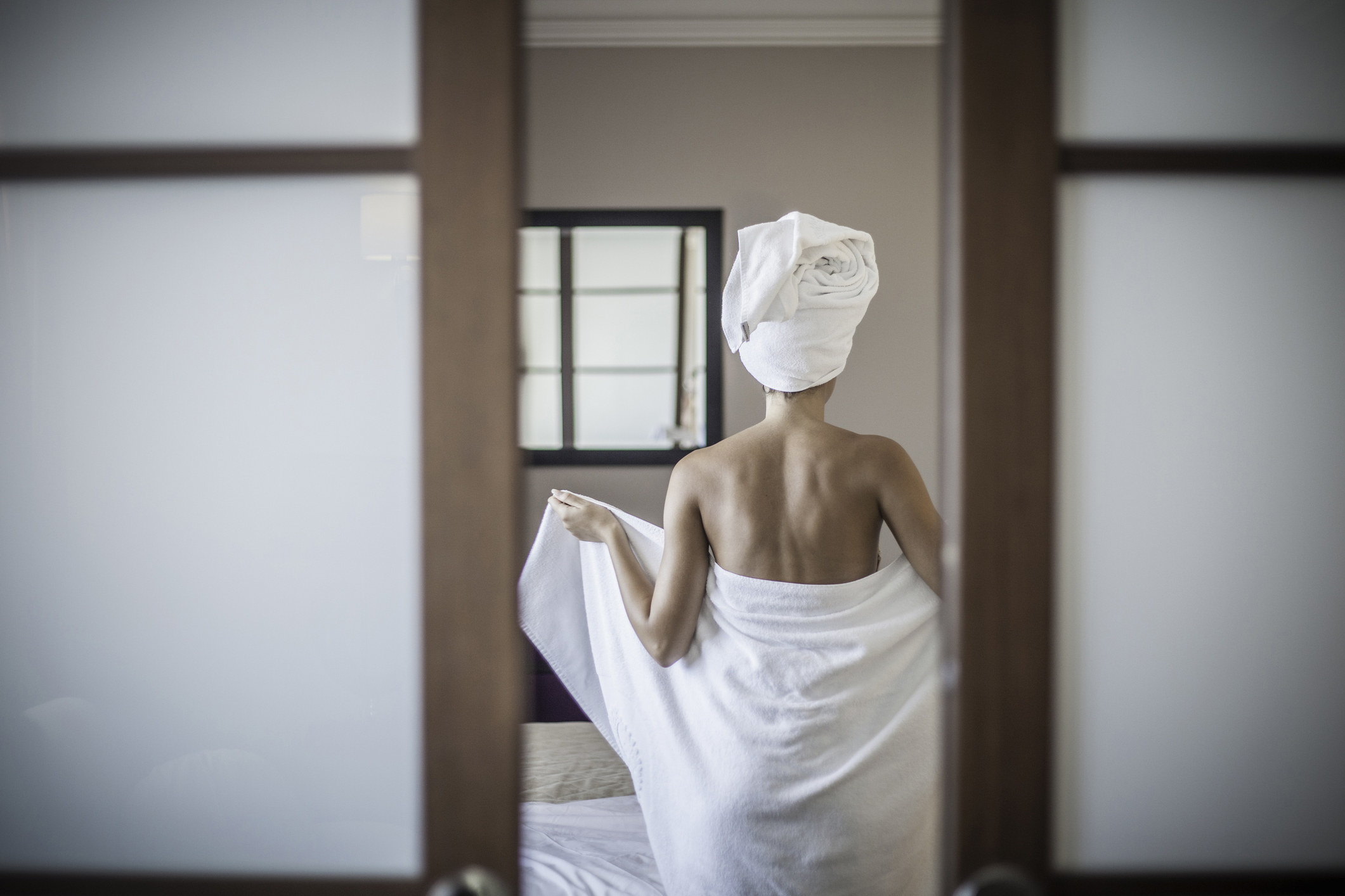 Reflection of someone in a full-length mirror closing a towel around them with a towel on their head