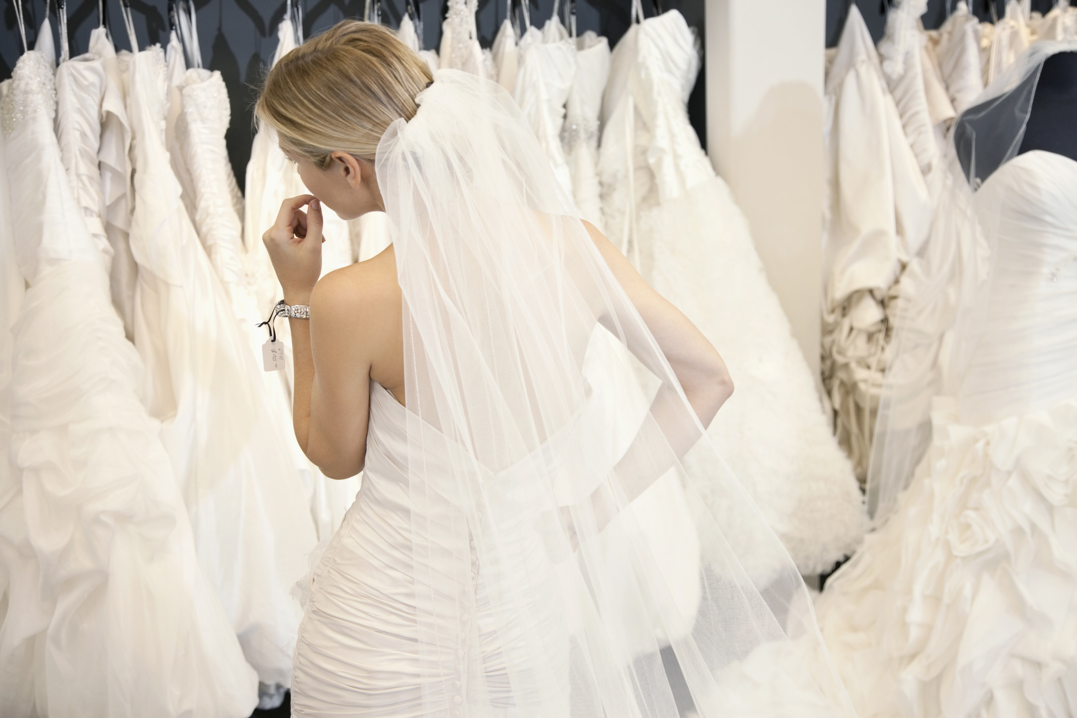 Bride looking at many different wedding dresses