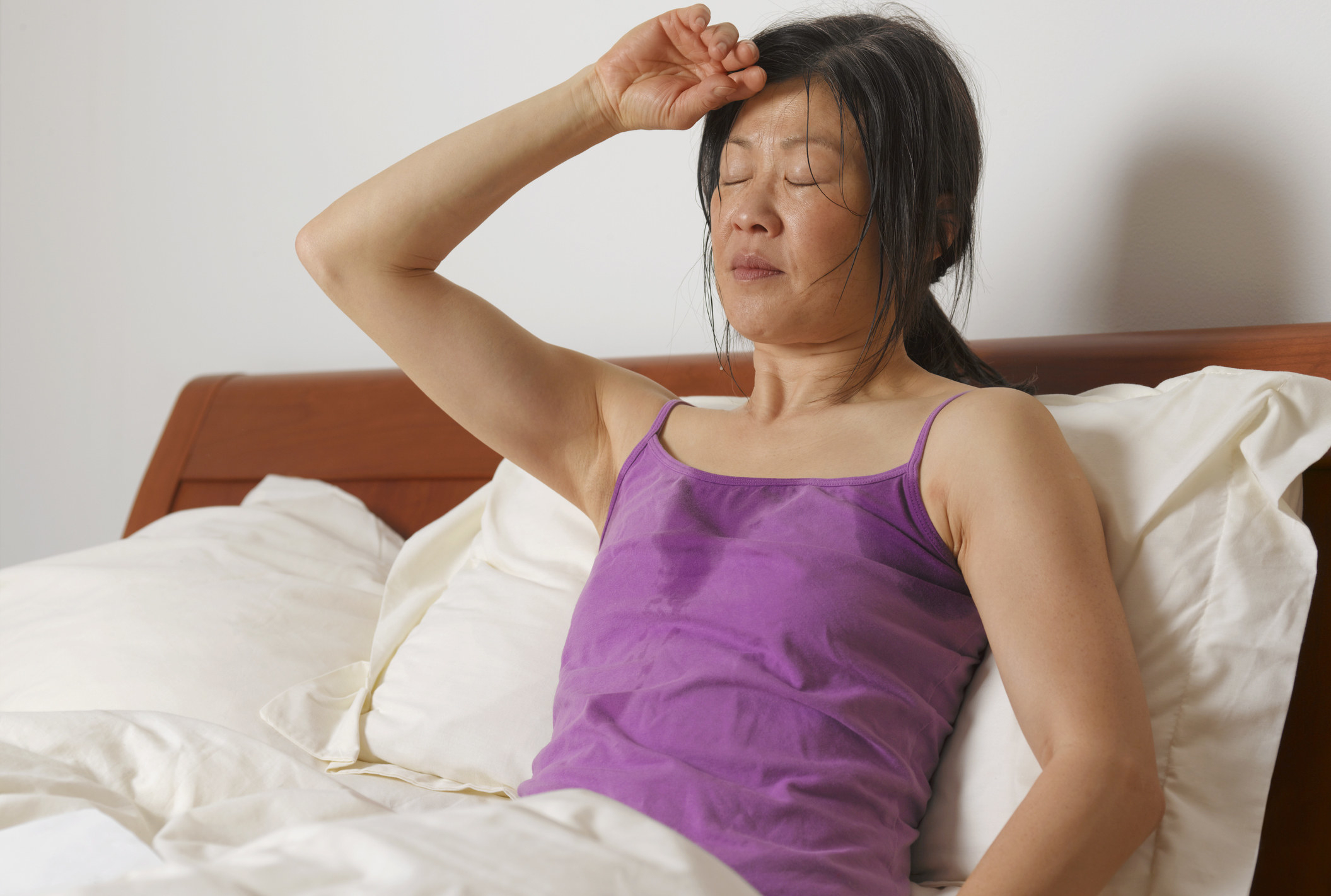 Someone leaning against pillows in bed wearing a spaghetti-strap tank top that has sweat around the neck and armpits, hair in a ponytail, wiping their forehead