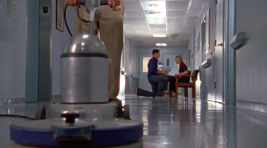 Person on one knee in a hospital hallway