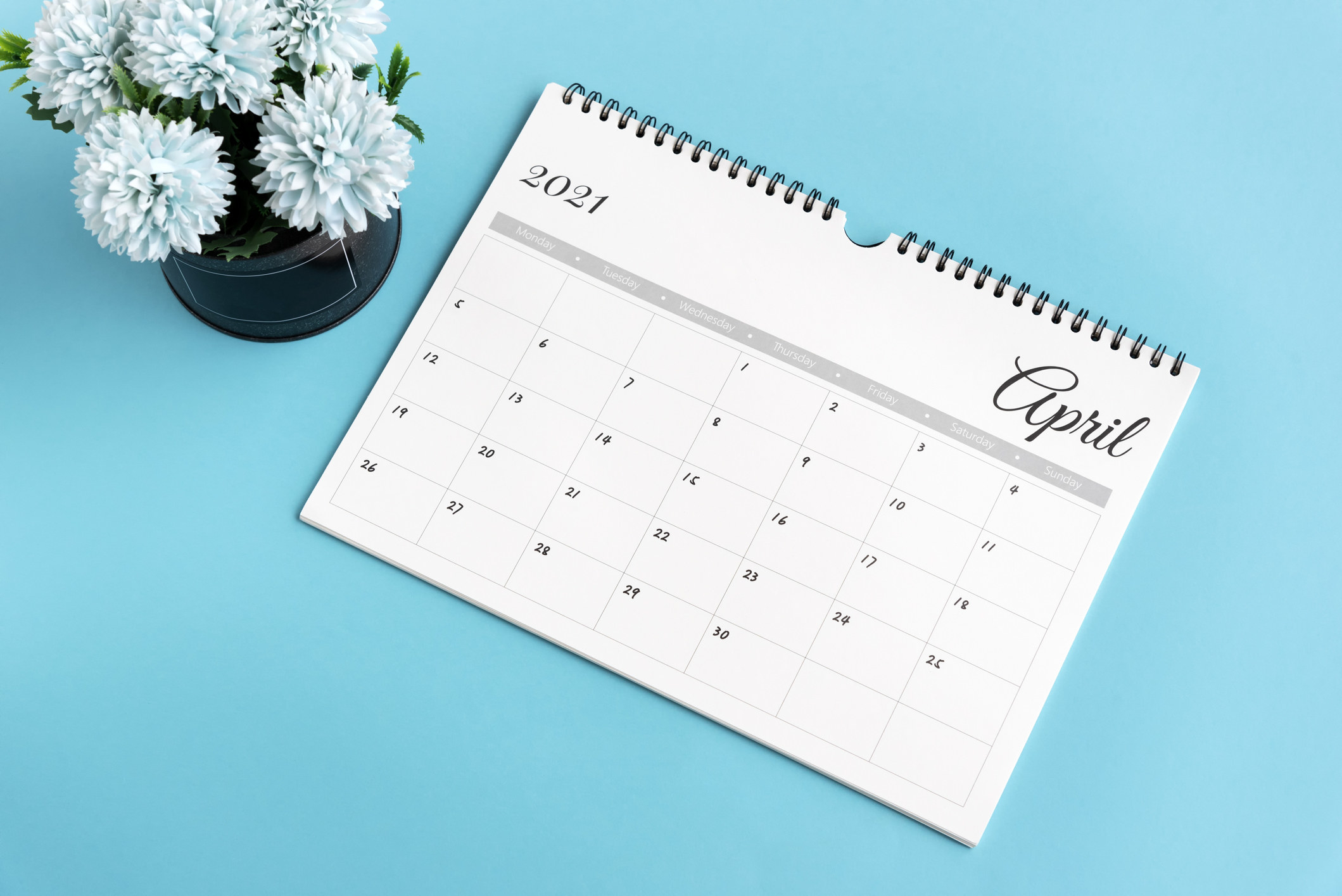 A spiral bound 2021 calendar opened to April, sitting next to a small pot of flowers