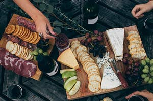 bottles of wine surrounded by beautiful boards of meat and cheese