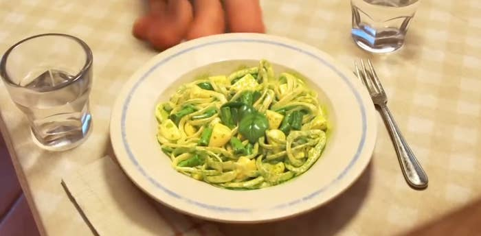 A screenshot of the trenette al pesto pasta from Luca, it has long thin noodles with green beans , yellow potato, and a sprig of basil on top