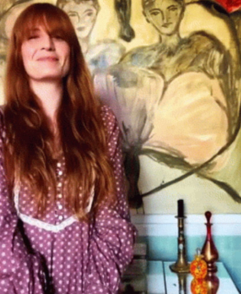 Florence Welch smiling while listening to music in her home