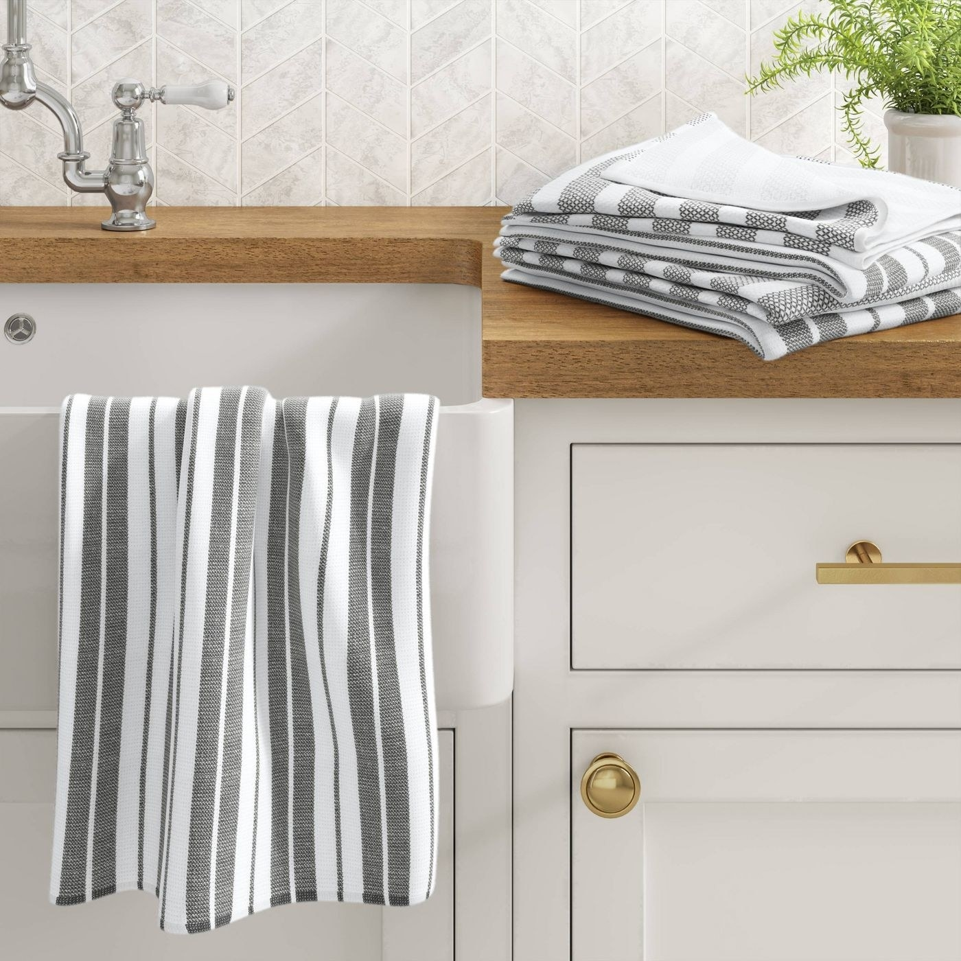 the gray striped towels on a counter and hanging on the edge of a sink