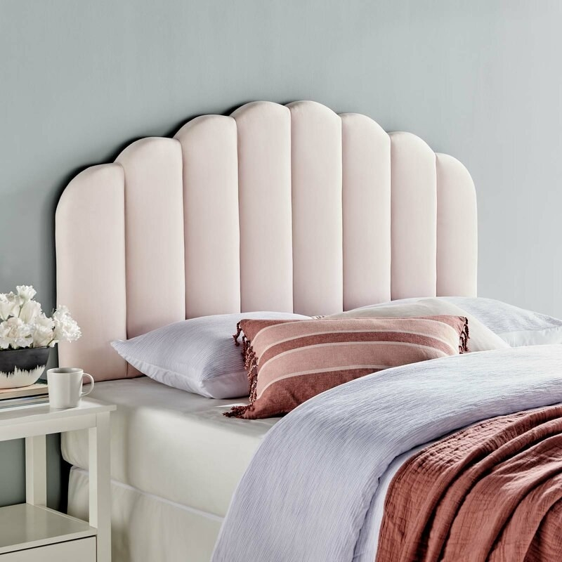 The pale pink panel headboard