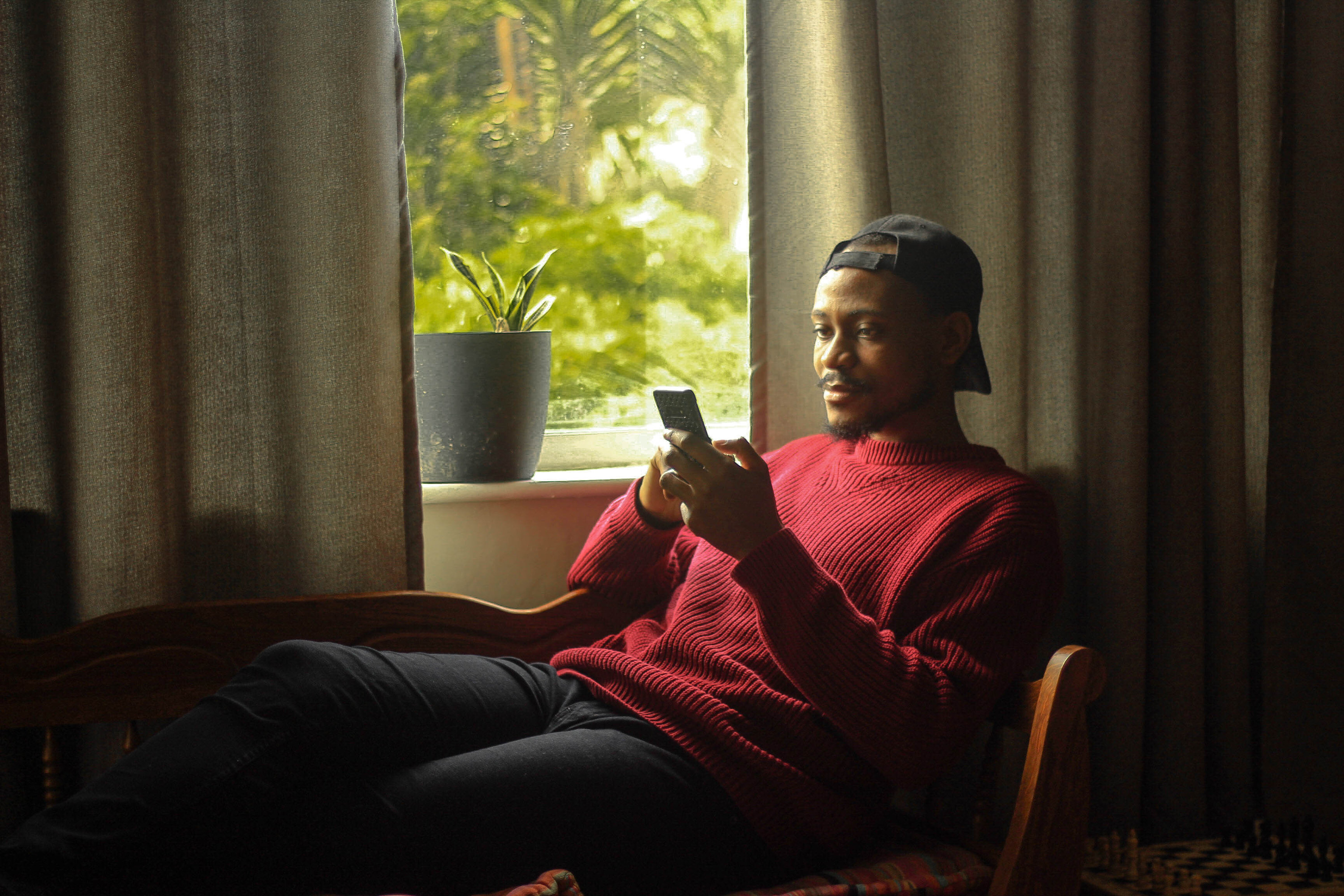 A guy with a backwards cap, sweater, and pants, lounging by a window looking at his phone