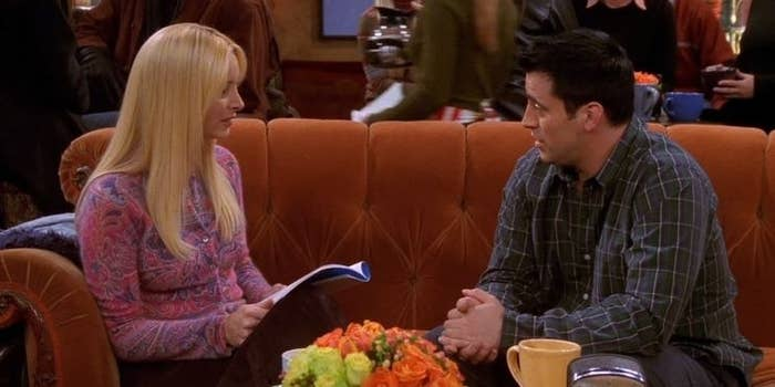 Joey and Phoebe sit on the orange couch of the Central Perk coffee shop.