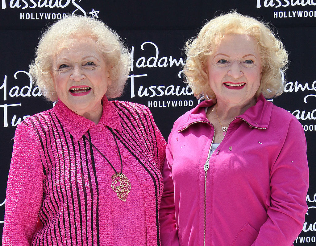 Betty White standing with her wax figure in Hollywood