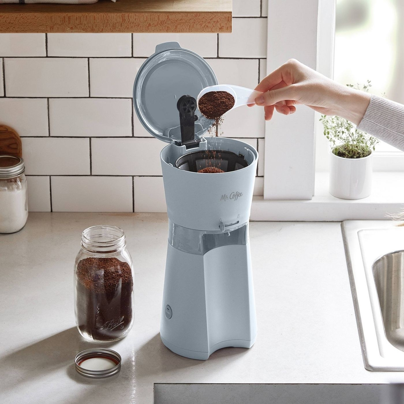 the small grey coffee maker on a counter