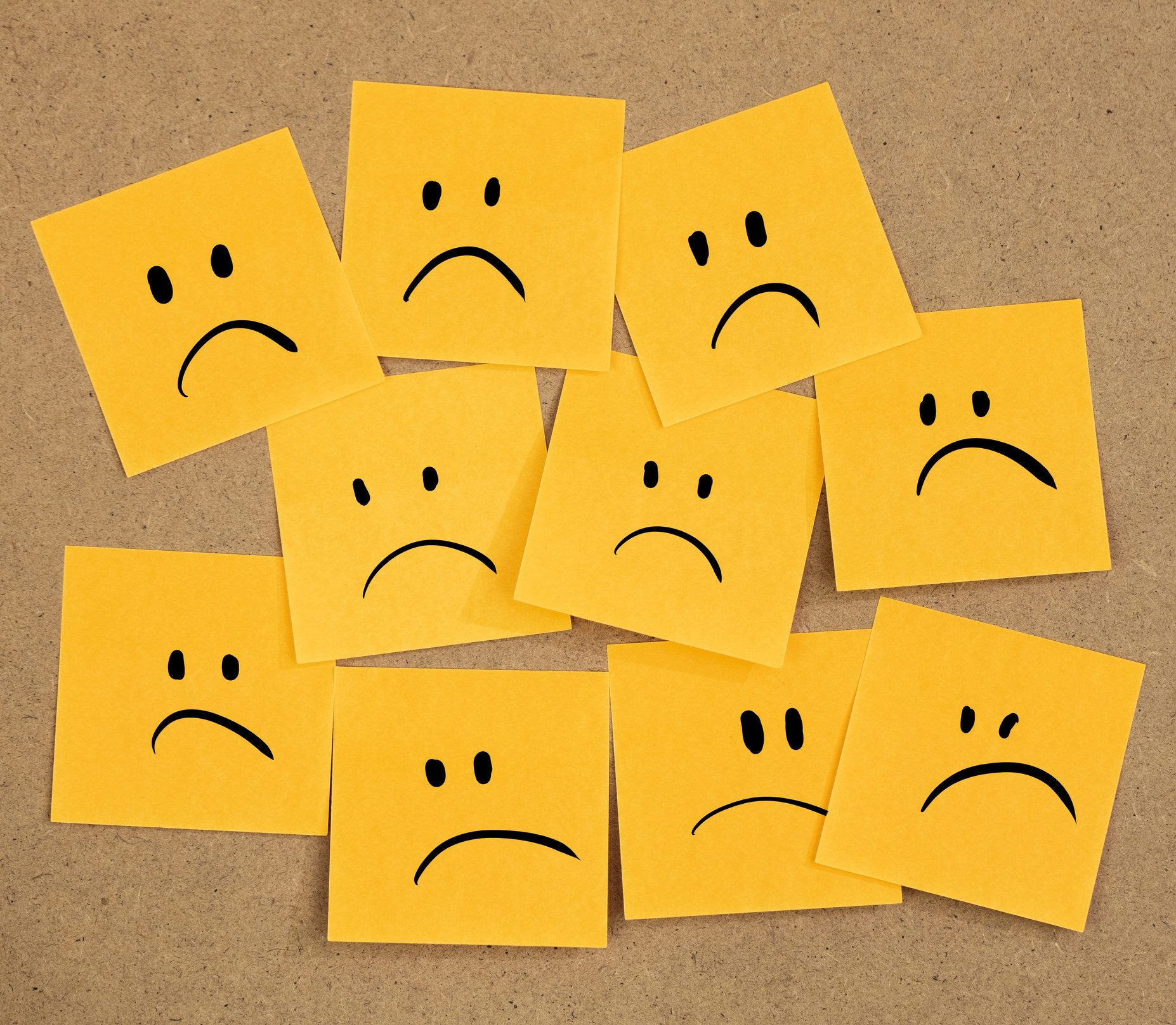 Ten post-it notes with sad faces on them arranged on a corkboard