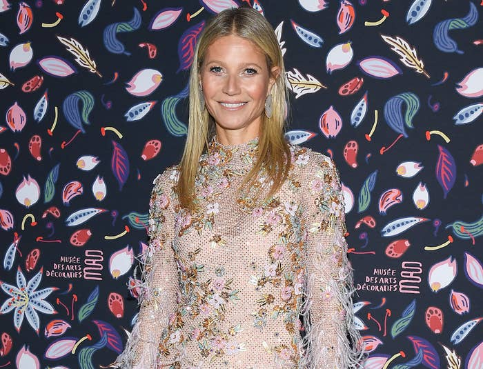 Gwyneth smiles while wearing a pink long sleeve dress with feathers and flowers