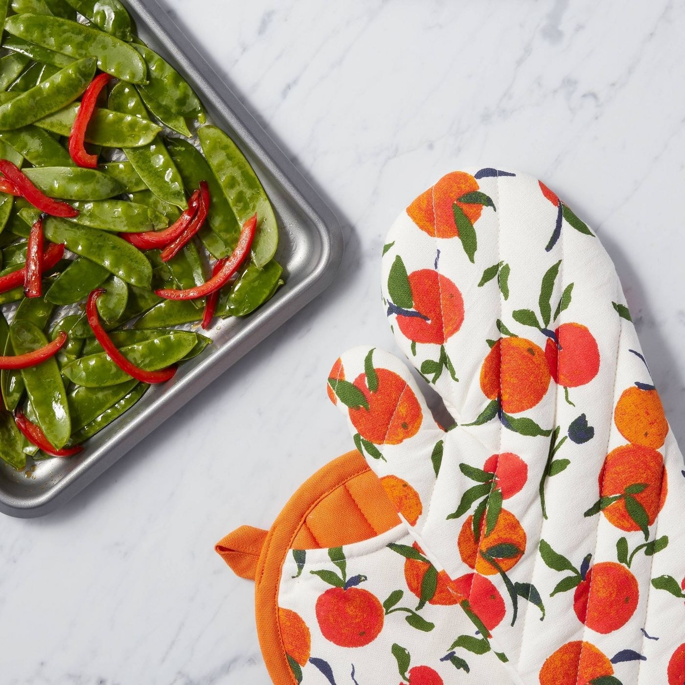 the orange patterned mitt and potholder next to a sheet pan of vegetables