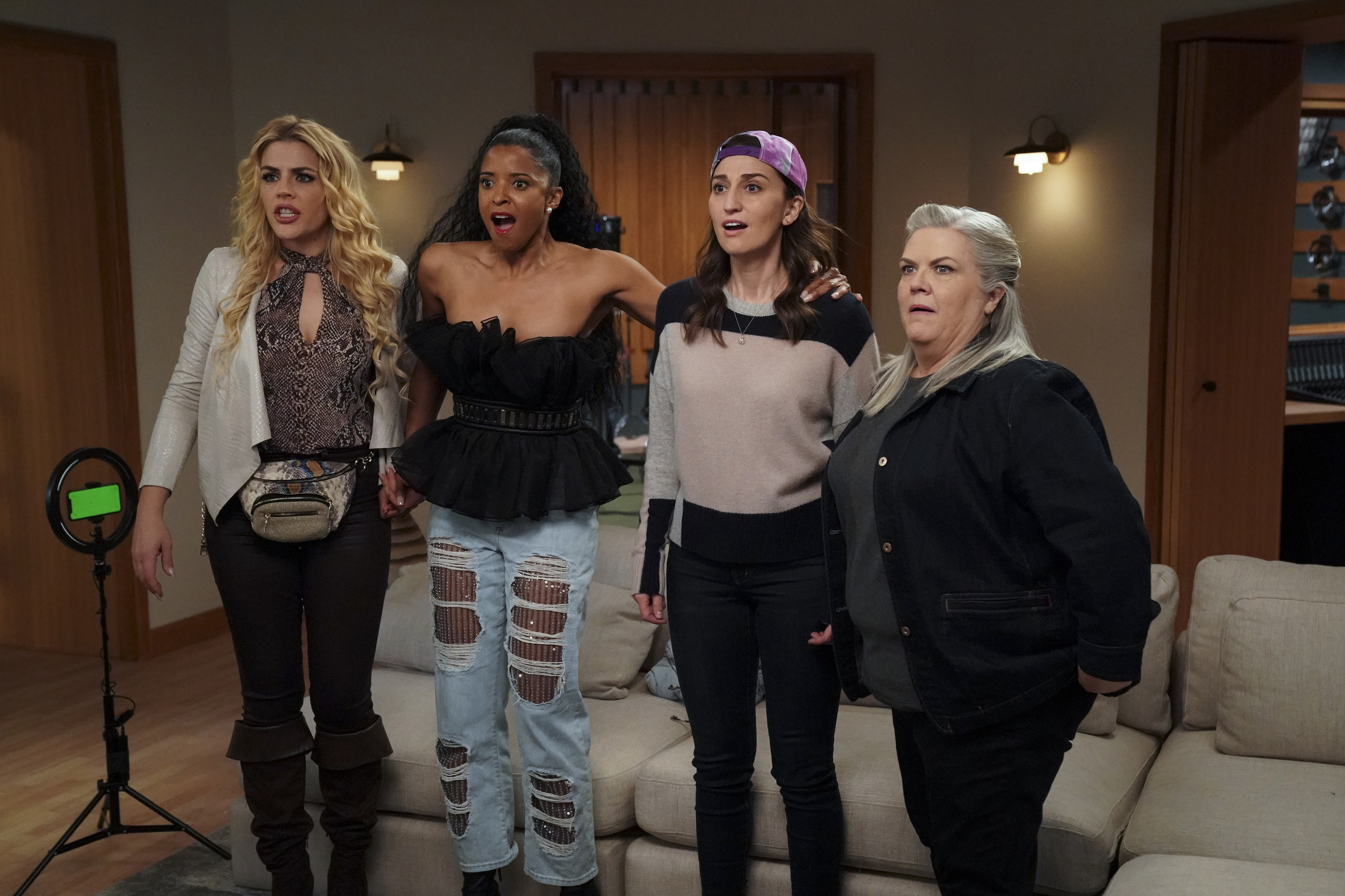 """Busy Philipps, Renée Elise Goldsberry, Sara Bareilles, and Paula Pell look surprised in a still image from the third episode of """"Girls5eva"""""""