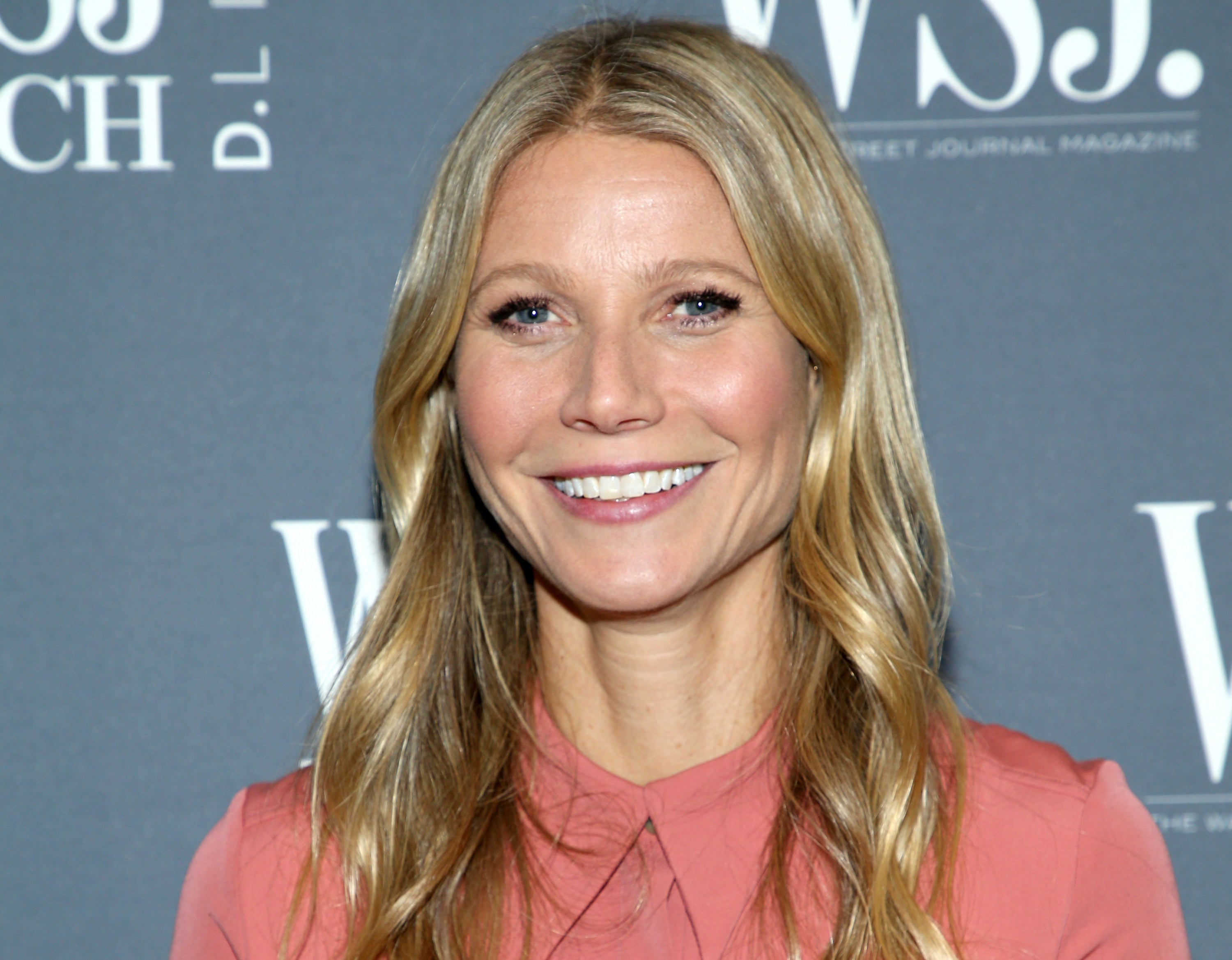 Gwyneth smiles in a pink shirt at an event