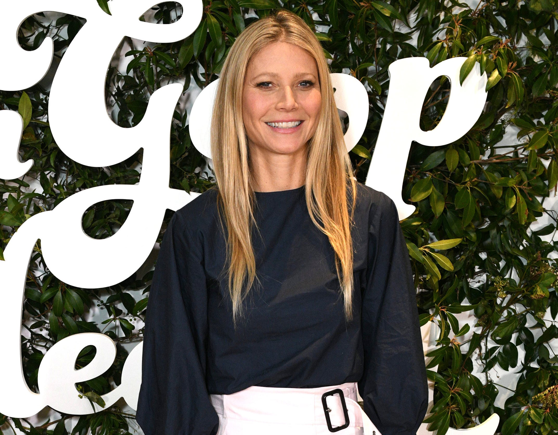 Gwyneth smiles in a black blouse at a recent event