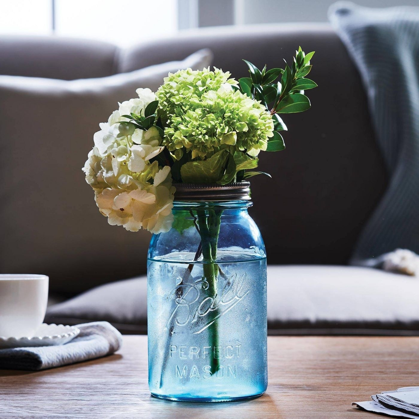 the blue jar with flowers in it