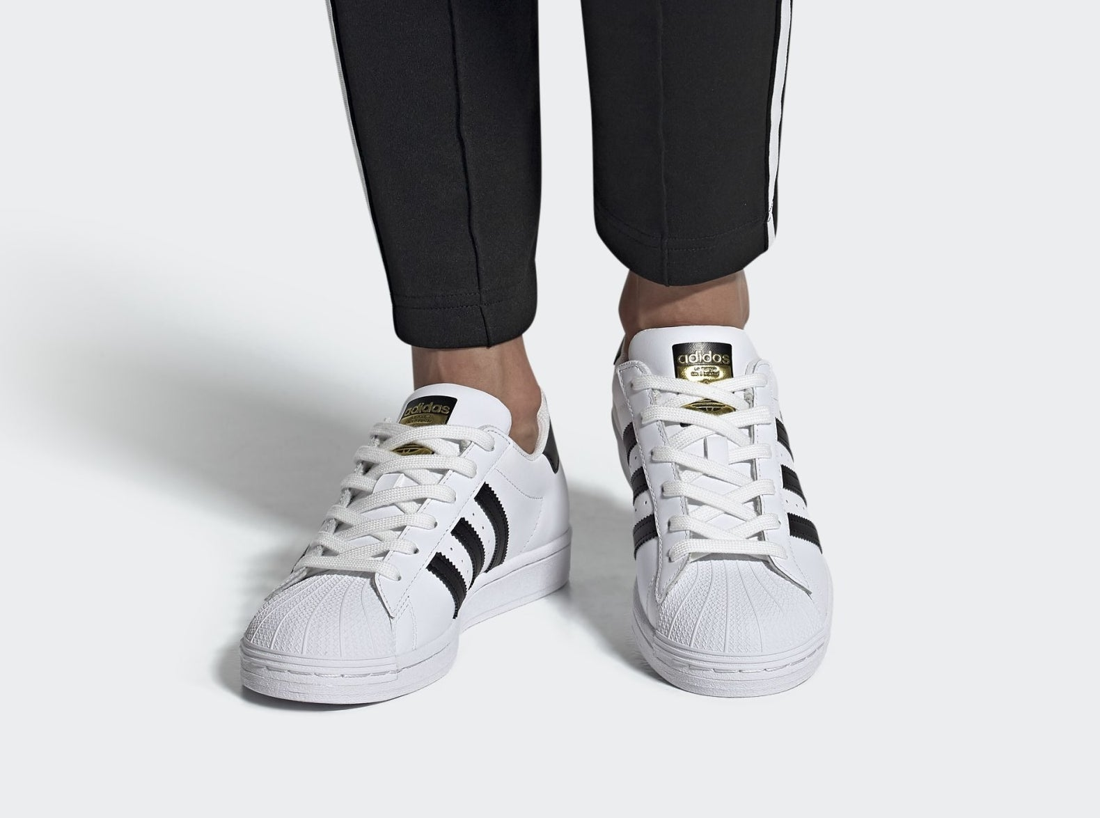 model wearing the white superstar adidas sneakers with black stripes