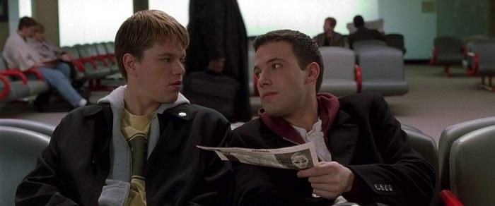 Matt Damon and Ben Affleck sitting in an airport terminal