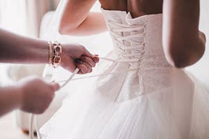 Someone helping a bride cinch the back of their gown